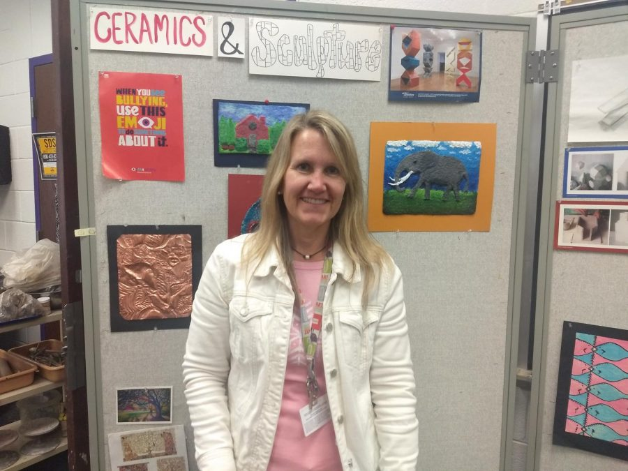 Ms.+Schutte+stands+in+front+of+student+artwork.