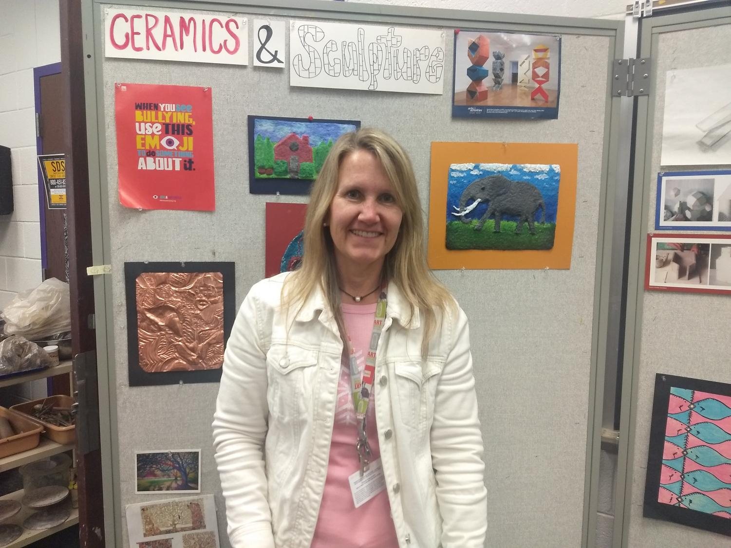Ms. Schutte stands in front of student artwork.